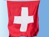 Des drapeaux, vaisselles et serviettes, ballons et guirlandes avec la croix Suisse.